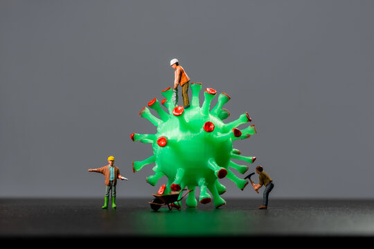 Miniature workers take a sample from a virus model, on a gray background close-up. Taking an analysis For the covid-19 test. Miniature models of people destroy and investigate the virus.