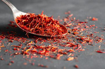 Heap of dried saffron spice in spoon on dark rustic background, spices and herbs concept (Crocus sativus)