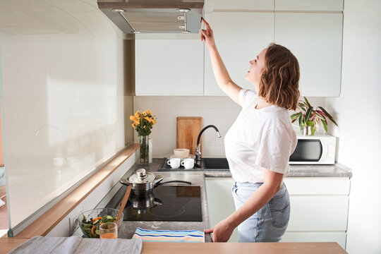 Woman select mode on cooking hood