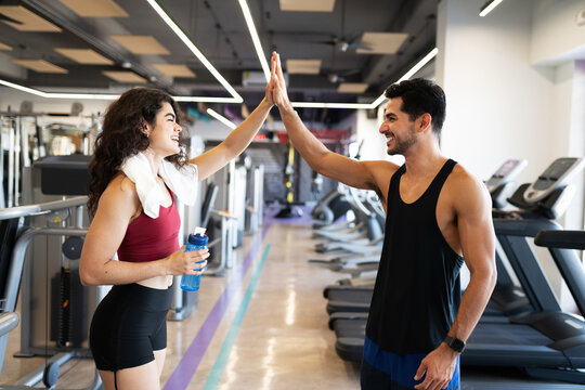 Young woman and man laughing at the gym