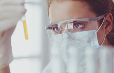 Researcher, doctor, scientist or laboratory assistant working with plastic medical tubes in modern lab or hospital