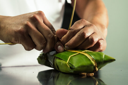 Peruvian hands tying a traditional tamale with banana leaves