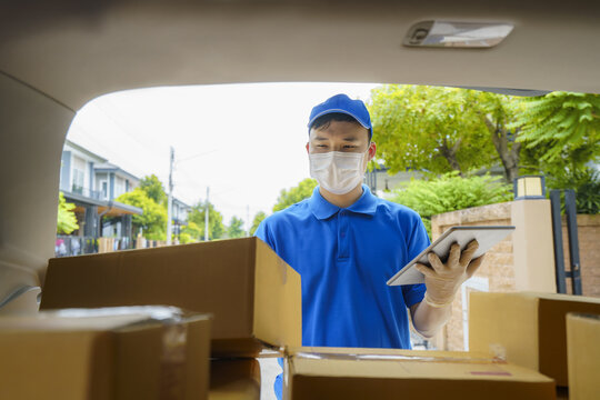 Asian Delivery man services courier working with cardboard boxes on van during the Coronavirus (COVID-19) pandemic, courier wearing medical mask and latex gloves for safety.