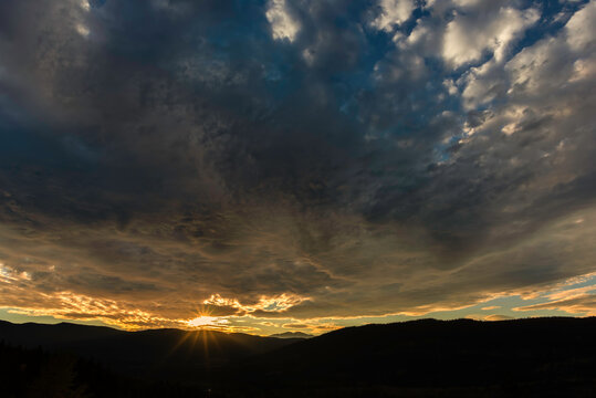 A dramatic sunset with the huge cloudy sky over black silhouettes of mountains