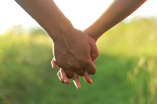 Man with a young woman holding hands walking