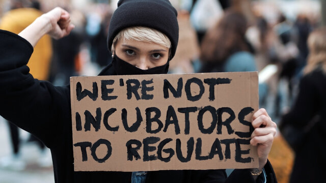 Womens march. Young woman with face mask holding banner sign - We are not incubators to regulate. protest against strict abortion laws. High quality photo