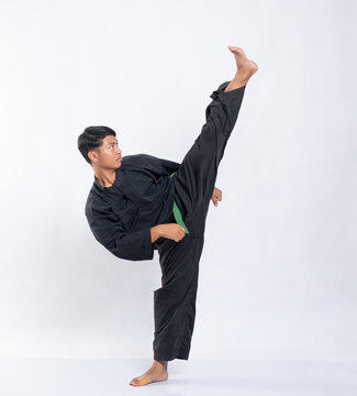 Asian men wearing pencak silat uniforms with green belts kicking one leg up high while on the isolated background