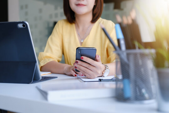 Young asian business woman using smart phone for contact customer on wooden desk in office. Business portrait concept.