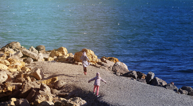 Photo two kids running by the sea on the embankment
