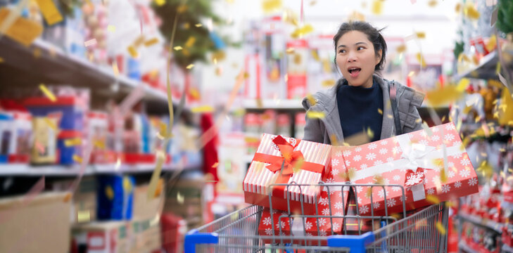 asian female woman customer happiness joyful hand pull shopping cart with full of presents gift box in shopping mall department store christmas festive background