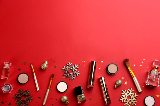 Flat lay composition with decorative cosmetic products on red background, space for text. Winter care