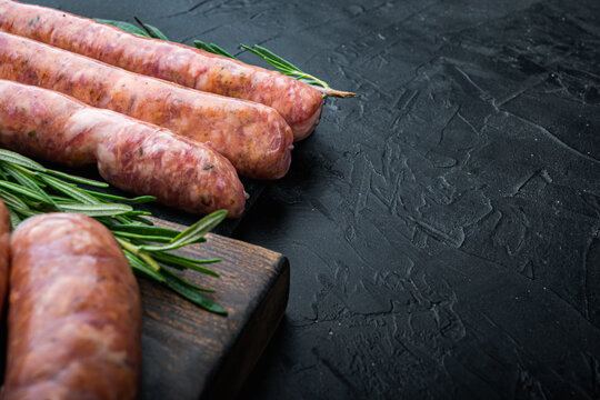 Raw homemade beef sausages with space for text, on black background