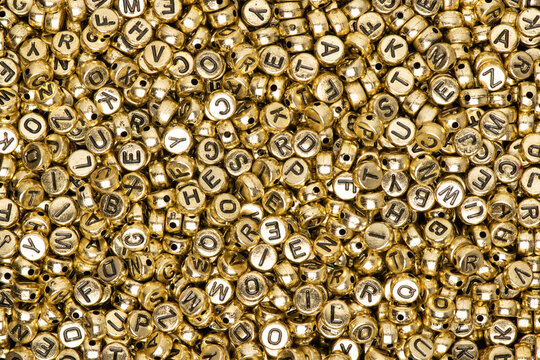 Metallic gold English alphabet beads background