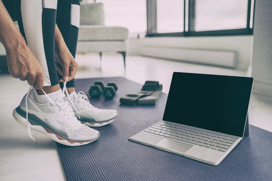 Home workout with laptop. Online fitness class . Woman getting ready for exercising tying her running shoes with technology device streaming on black screen.