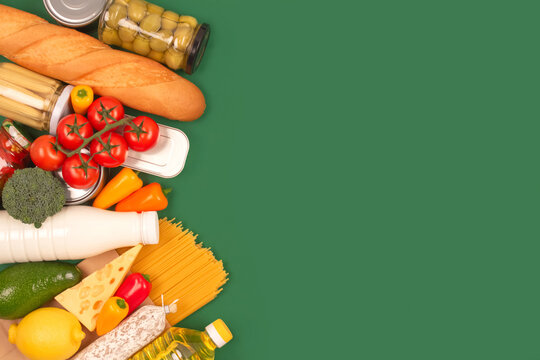 Different groceries, food donations on green background with copyspace - pasta, fresh vegatables, canned food, baguette, cooking oil, tomatoes, cheese. Food donations, food bank, food delivery concept