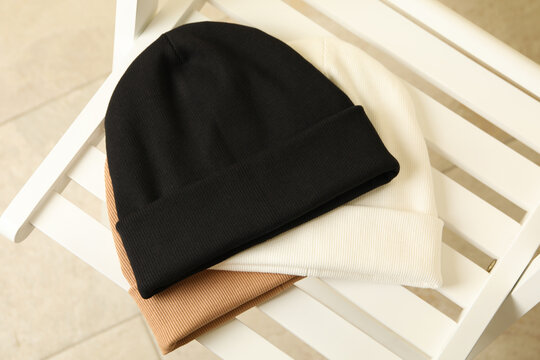 Three stylish beanies on wooden chair, top view
