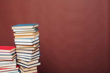 many stacks of educational books for exams in the library on the brown background of the university