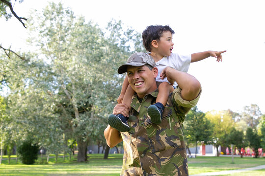 Exited little boy sitting on dad neck and pointing away. Caucasian father holding son legs, smiling, wearing army uniform and walking in park. Family reunion, fatherhood and returning home concept