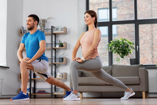 sport, fitness, lifestyle and people concept - smiling man and woman exercising and doing lunge at home