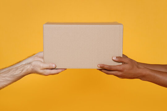 Close up cropped men hold in hands give brown clear blank paper empty cardboard box isolated on yellow background Packaging template mock up Delivery service concept Free Copy space Advertising area.