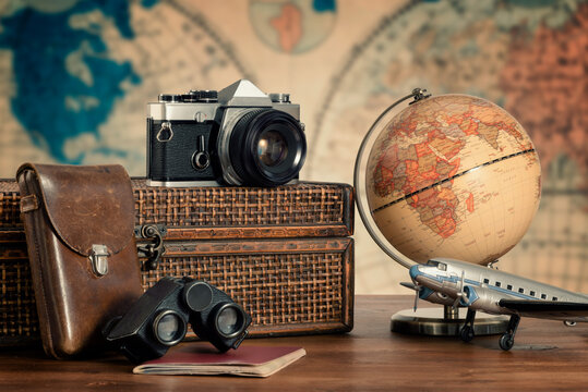 Vintage travel concept. Old accessories used to travel, vintage camera, binoculars, old suitcase, an old propeller airplane and a globe map. Toned Image. Selective focus.