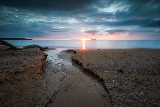 Amazing sunrise view with colorful sky at a sandy sea coast