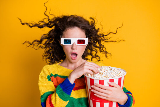 Photo of surprised funky young brunette lady hold popcorn watch movie wear spectacles sweater isolated on yellow color background