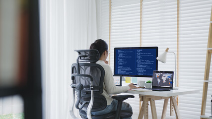 Back rear view of young asian woman, freelance data scientist work remotely at home coding...