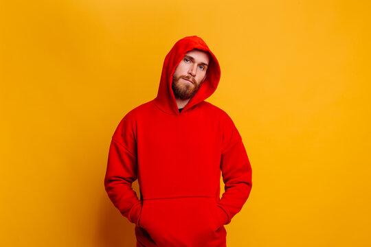 Happy  caucasian handsome brutal bearder man wearing warm red winter trendy fleece hoodie, studio shot, yellow background.