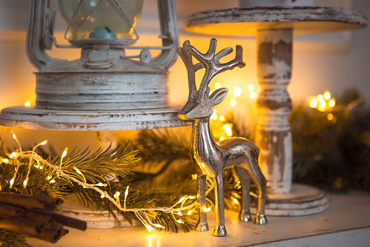 Christmas Decoration silver figure of a deer with branching horns, cinnamon sticks in festive lights garland yellow. New year, Christmas tree branch, white antique rustic decor. Copy space