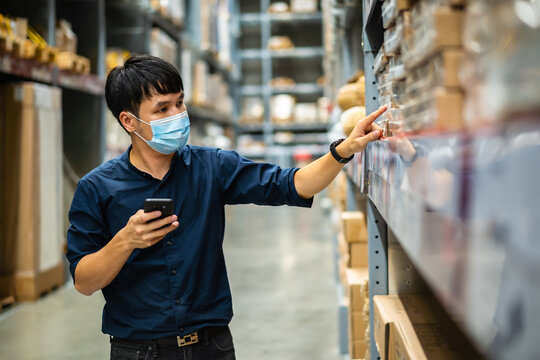 man worker with medical mask using smartphone to checking inventory in warehouse during coronavirus (covid-19) pandemic