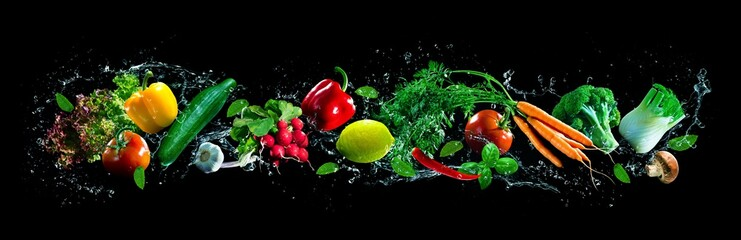 Fresh vegetables and water splashes on panoramic background