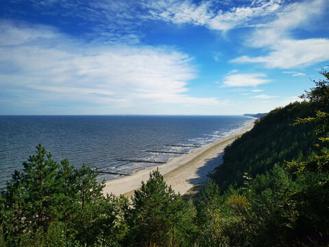 High panoramic view down to Usedom beach at baltic sea in Germany in summer through forest with blue cloudy sky and small hiking people.