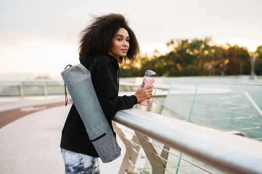 Attractive young african sportswoman carrying fitness mat