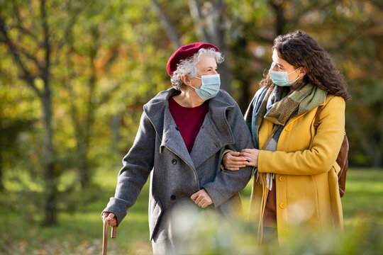 Senior woman with lovely girl wearing face mask at park