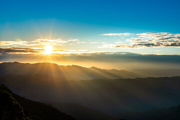 Landscape images of The morning sun, where a beautiful beam of light covers the mountain range, And the light reflected on the clouds in the sky, to nature background concept.