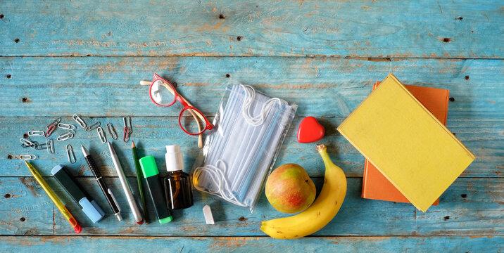 School supplies and COVID-19, corona virus prevention items on classroom desk with books,pens, eyeglasses.Back to school,education,learning,coronavirus precautions concept.