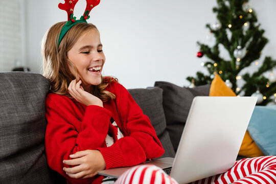 Happy nice girl wearing toy deer horns using laptop