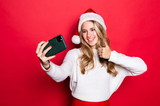 Portrait of a pretty woman with thumbs up wearing Christmas hat taking a selfie isolated over red background