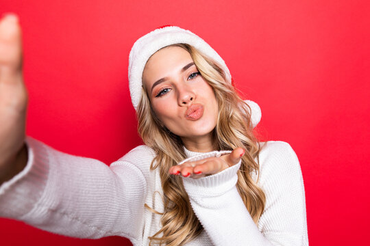 Self-portrait of woman in santa hat, sending air kiss, isolated over red background