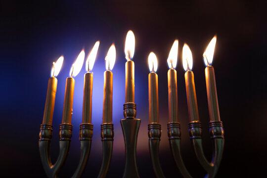 Lit Menorah in Celebration of Hanukah against Colored Background