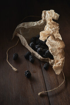 Blackberries spilled on the table from paper packaging