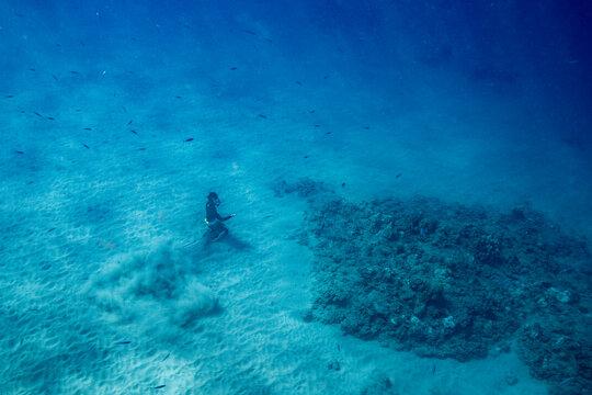 Free diver sits on ocean floor in clear waters of Hawaii