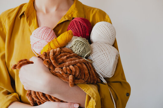Rolls of cotton ropes in woman hand. Knitting, crocheting, handm