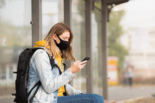 Woman in mask with a cell phone at a bus stop. Young female usin