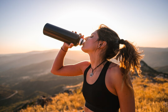 Close portrait young athlete woman drinking water from a bottle