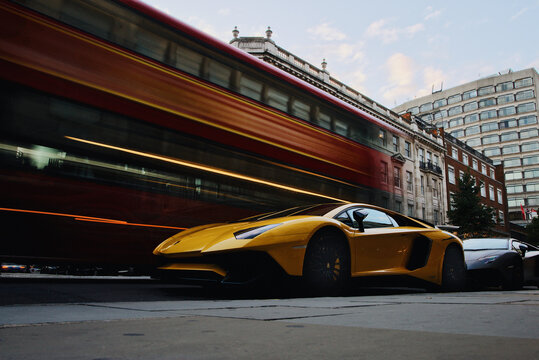 A Yellow Lamborghini Aventador SV parked on the street while a double decker bus passes by in London, UK on September 15, 2018
