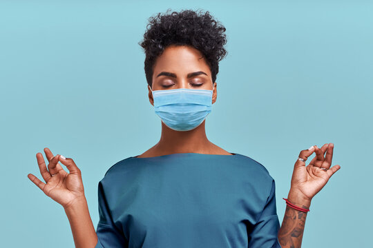 African American doctor meditation wear respiratory mask, no stress free relief at work concept, mindful peaceful young female paramedic practicing breathing yoga exercises on blue wall. Coronavirus