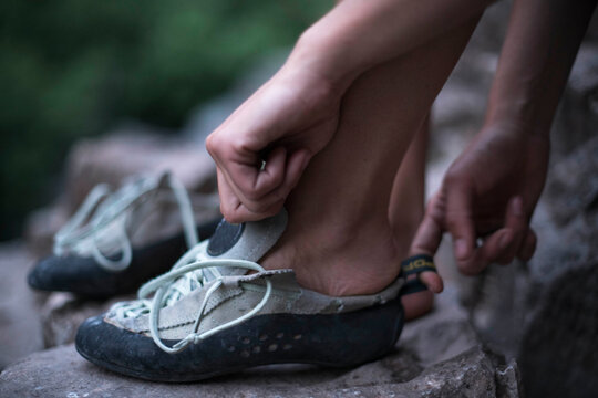 Low section of female hiker wearing shoes on rock