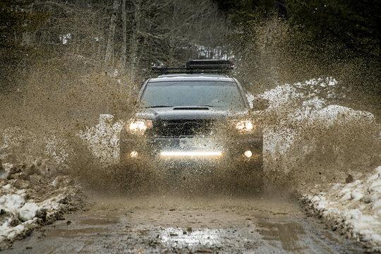Off-road car splashing dirt on road during winter